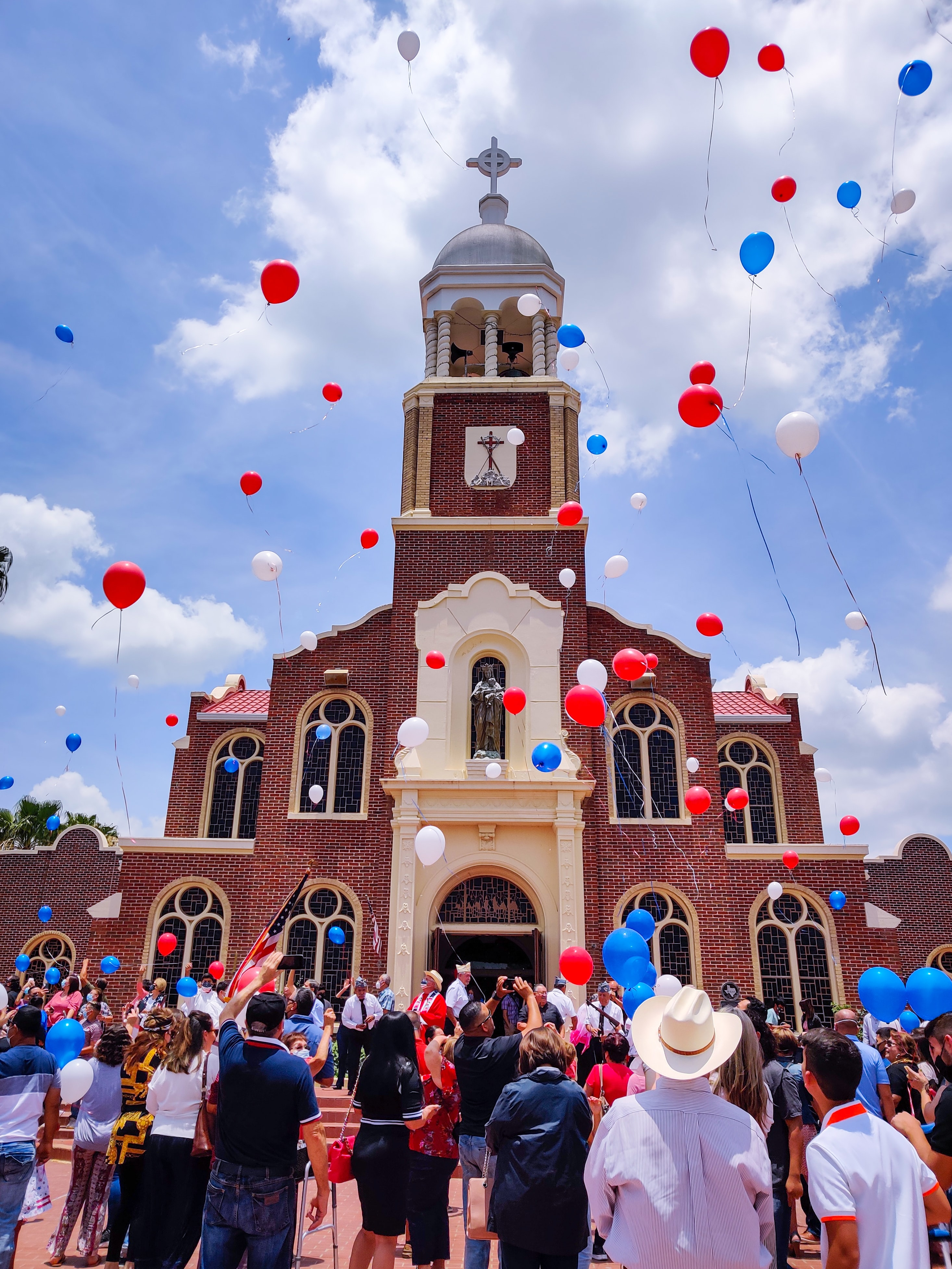 A group of people at a celebration in front of a church featureing red white and blue balloons
