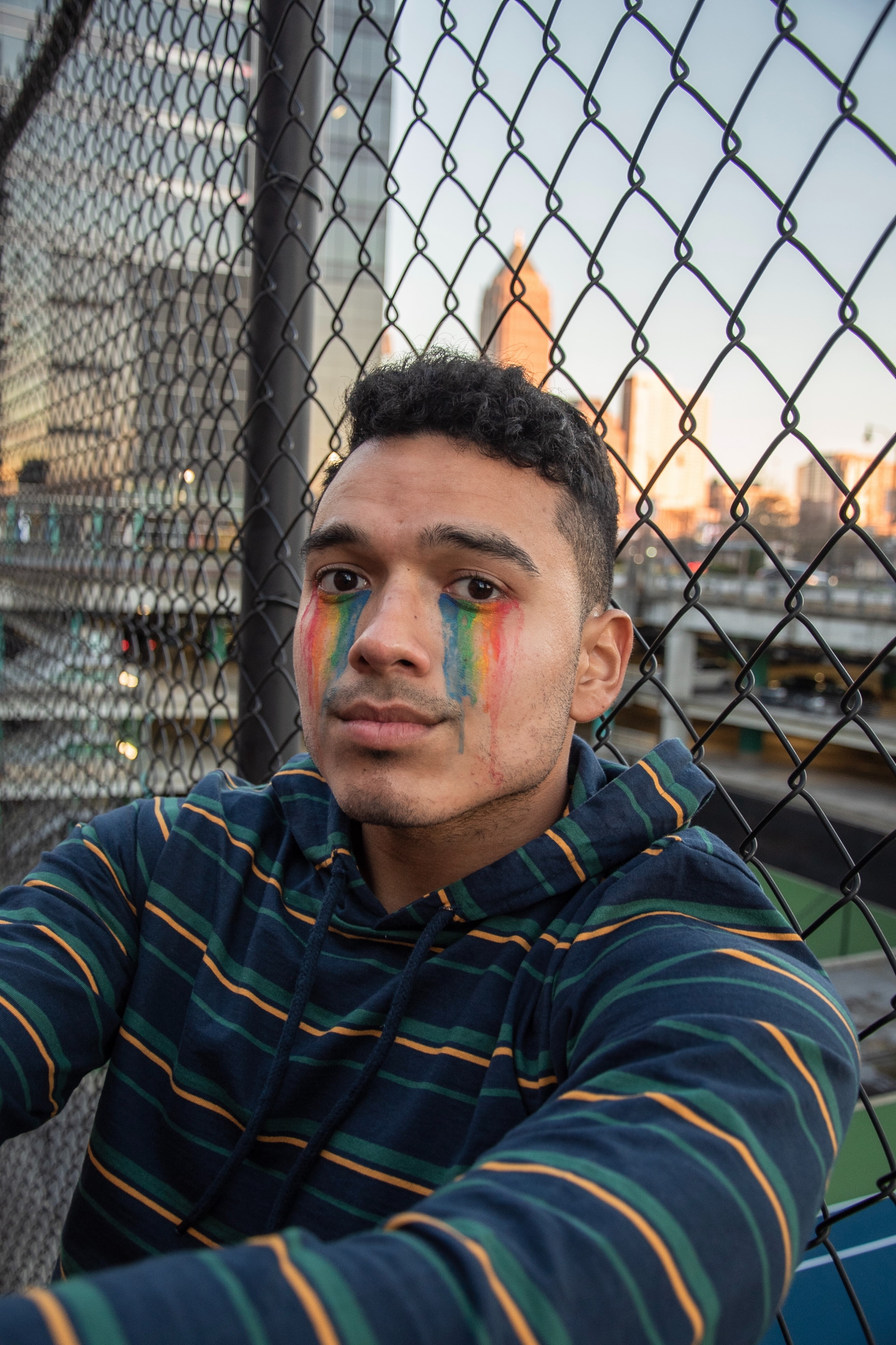 Yougn Hispanic man wearing a striped hoodie and rainbow face paint beneath his eyes