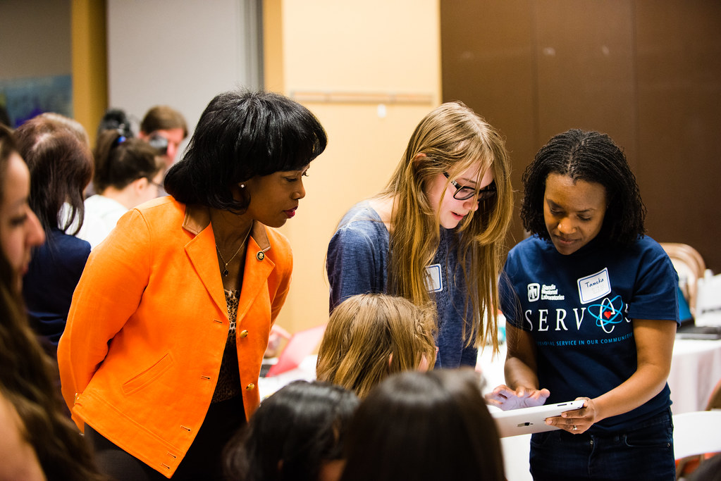 An African-American woman mentor observing young women students at a stem mentoring cafe event.