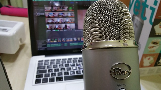 A microphone sits in front of a laptop.