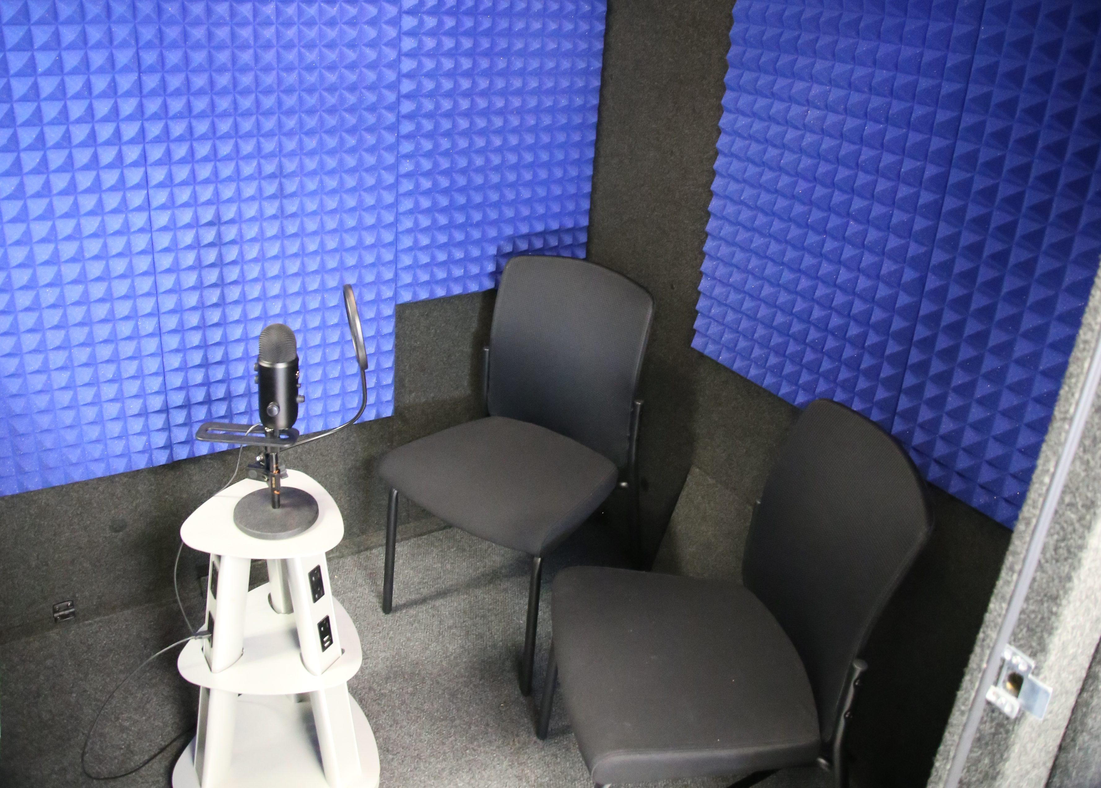 Two chairs sit in front of a microphone inside a soundbooth padded with foam.