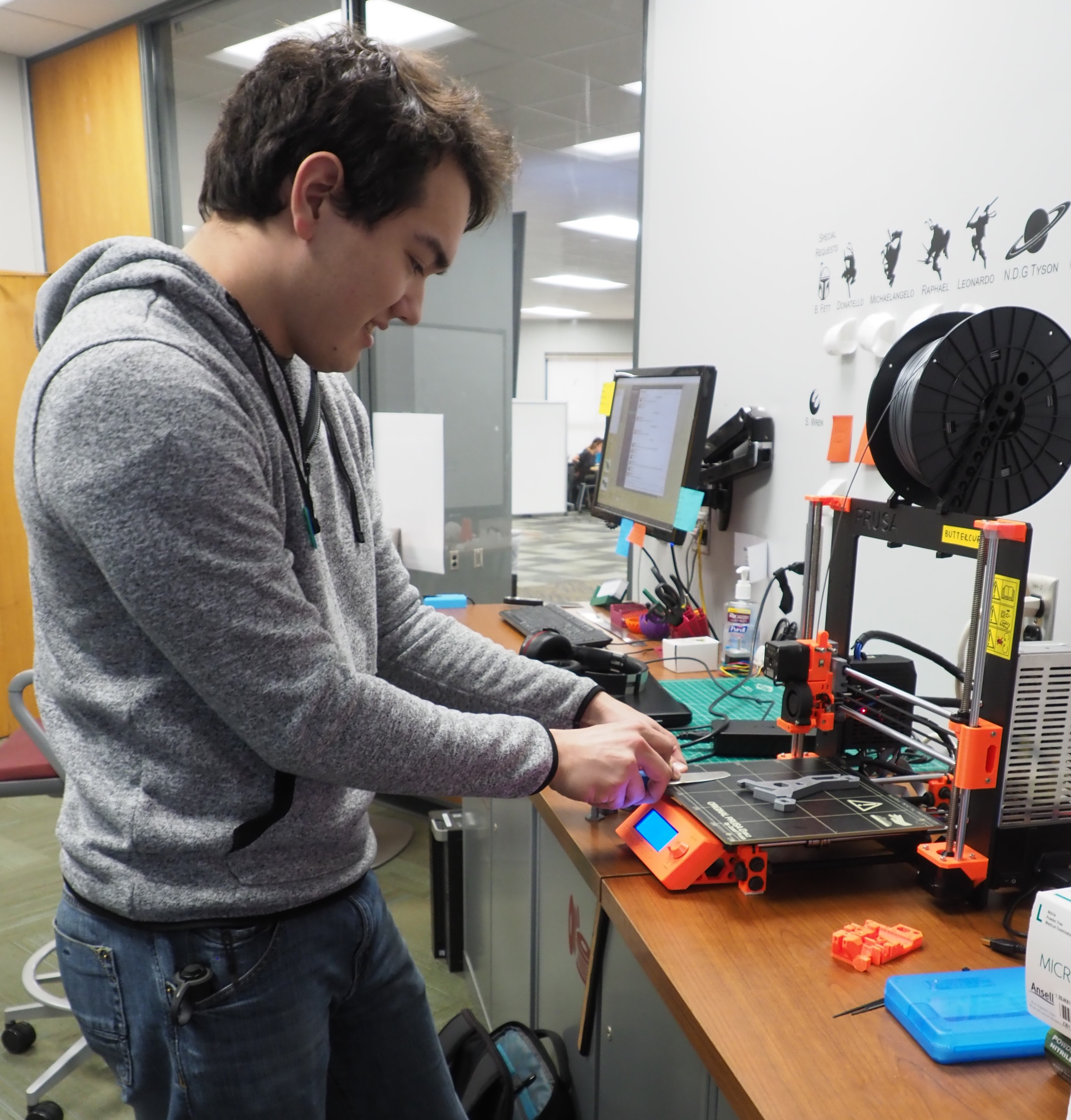 3D Design Studio staff work on a 3D printer