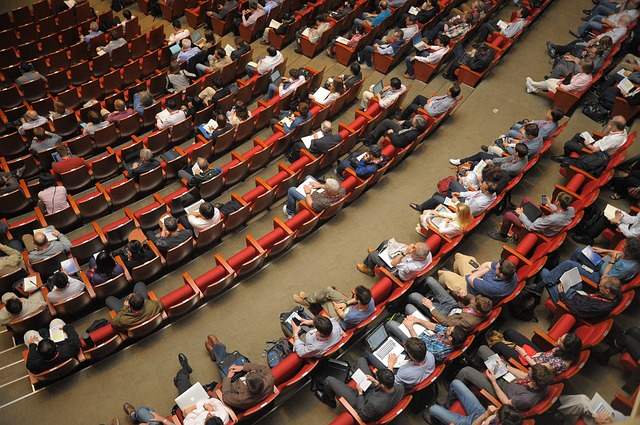 A crowd sits in auditorium seats.