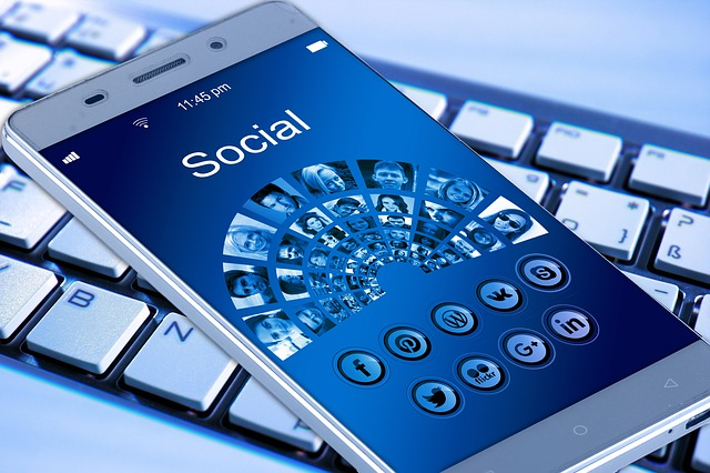 A cell phone displays images of people and social media logos with a keyboard in the background.
