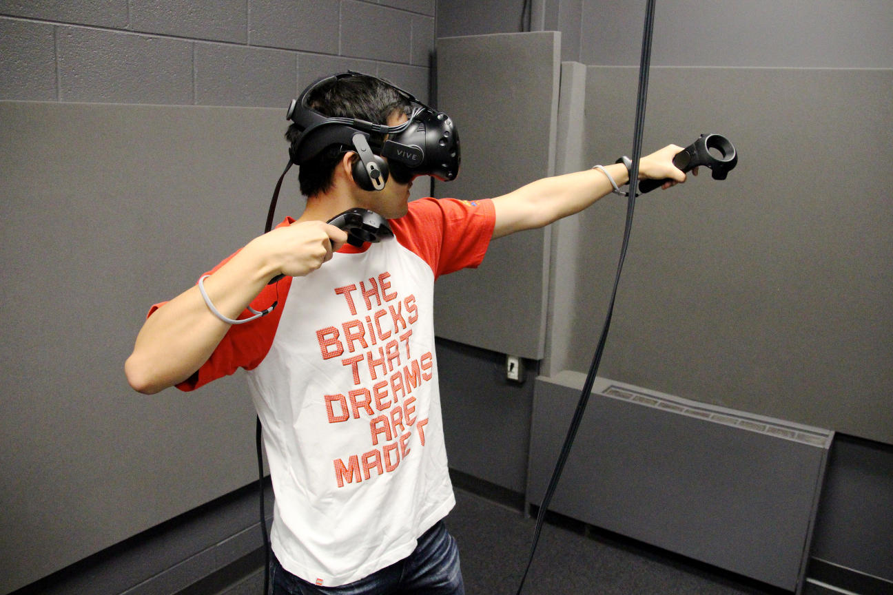 A student wearing a headset plays a virtual reality game.