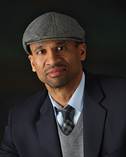 Jesse Washington wearing a gray cap and suit sitting in front of a black background.