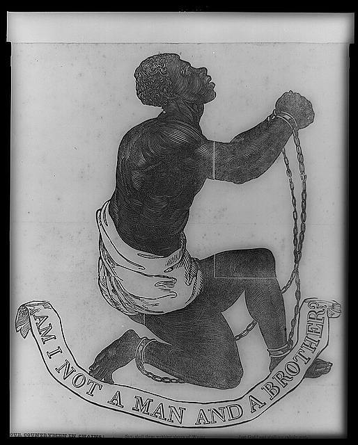human figure kneeling with chains on wrists and ankles. Motto reads am I not a man and brother