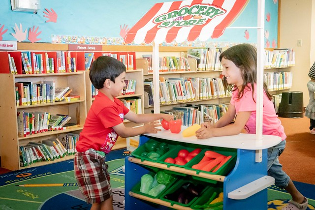 Two young children playing at a toy grocery store in a library.