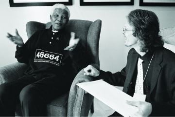 Verne Harris sitting next to Nelson Mandela, engaged in a conversation.