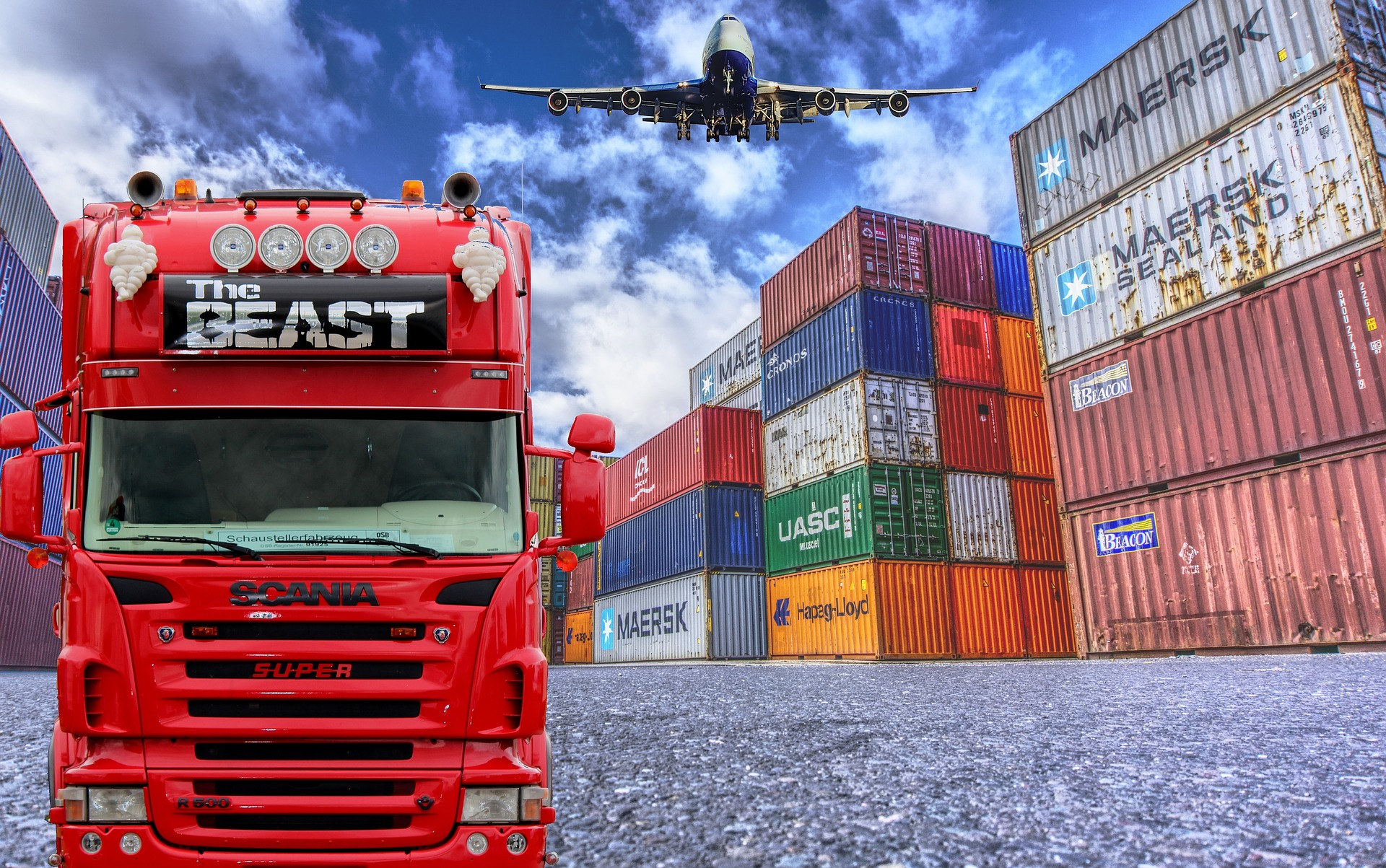 A supply chain represented by a truck and airplane passing through a storage area filled with large metal shipping containers.