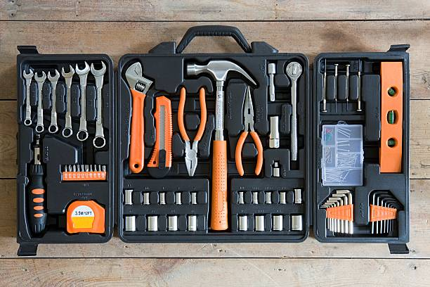 Image of an open tool kit full of tools, such as wrenches and hammers, many with orange handles.