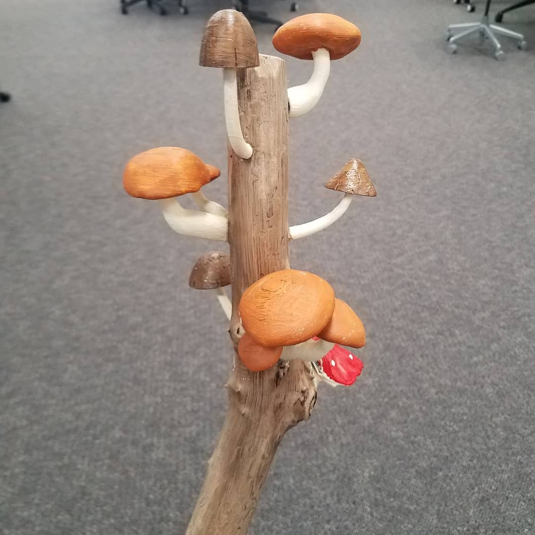 A wooden staff adorned with realistic mushrooms