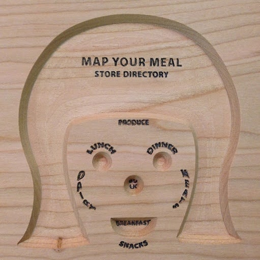 A wooden cutout of a grocery store layout, in the shape of a face.