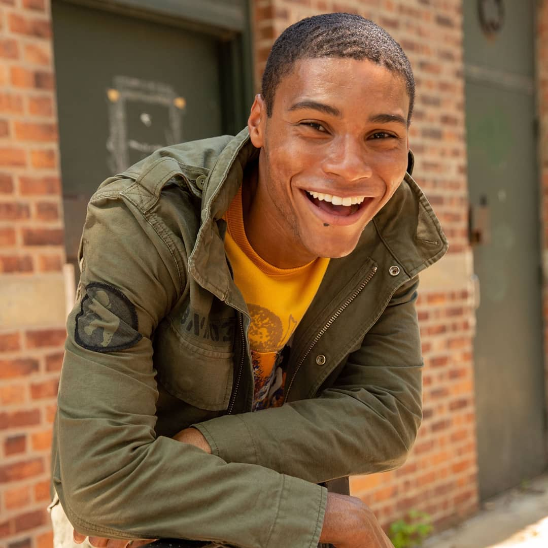A student smiles and leans on a brick wall.