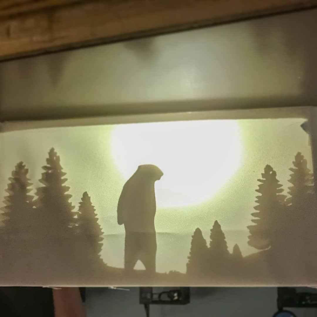 A CNC-carved lamp depicting a bear and trees, backlit.