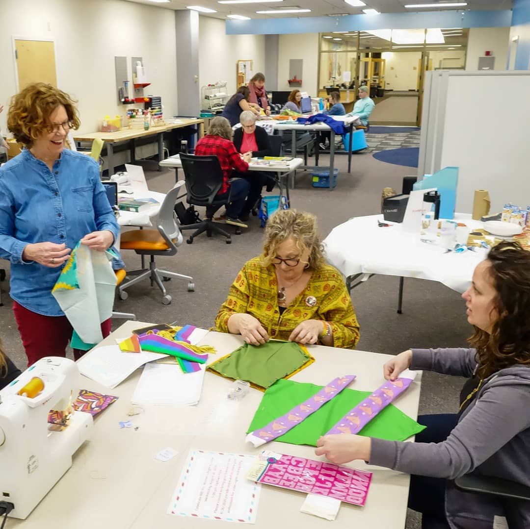 Three people talk and sew around a table covered in fabric and sewing supplies.