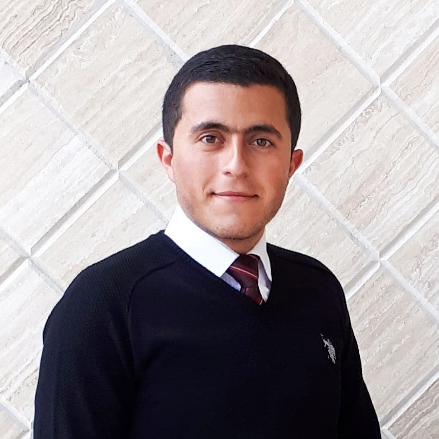 A student wearing a tie and dark sweater.