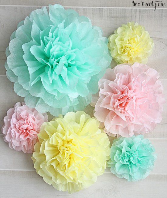 A collection of six tissue-paper flowers, in green, yellow, and pink.