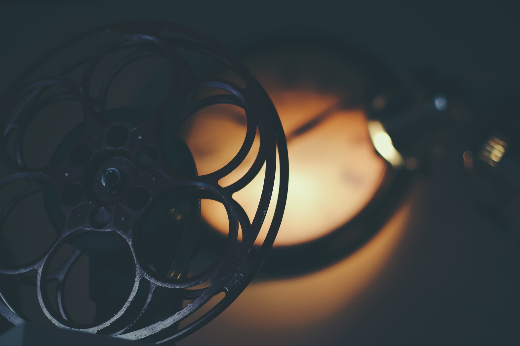 An old film reel with a circle of light behind it