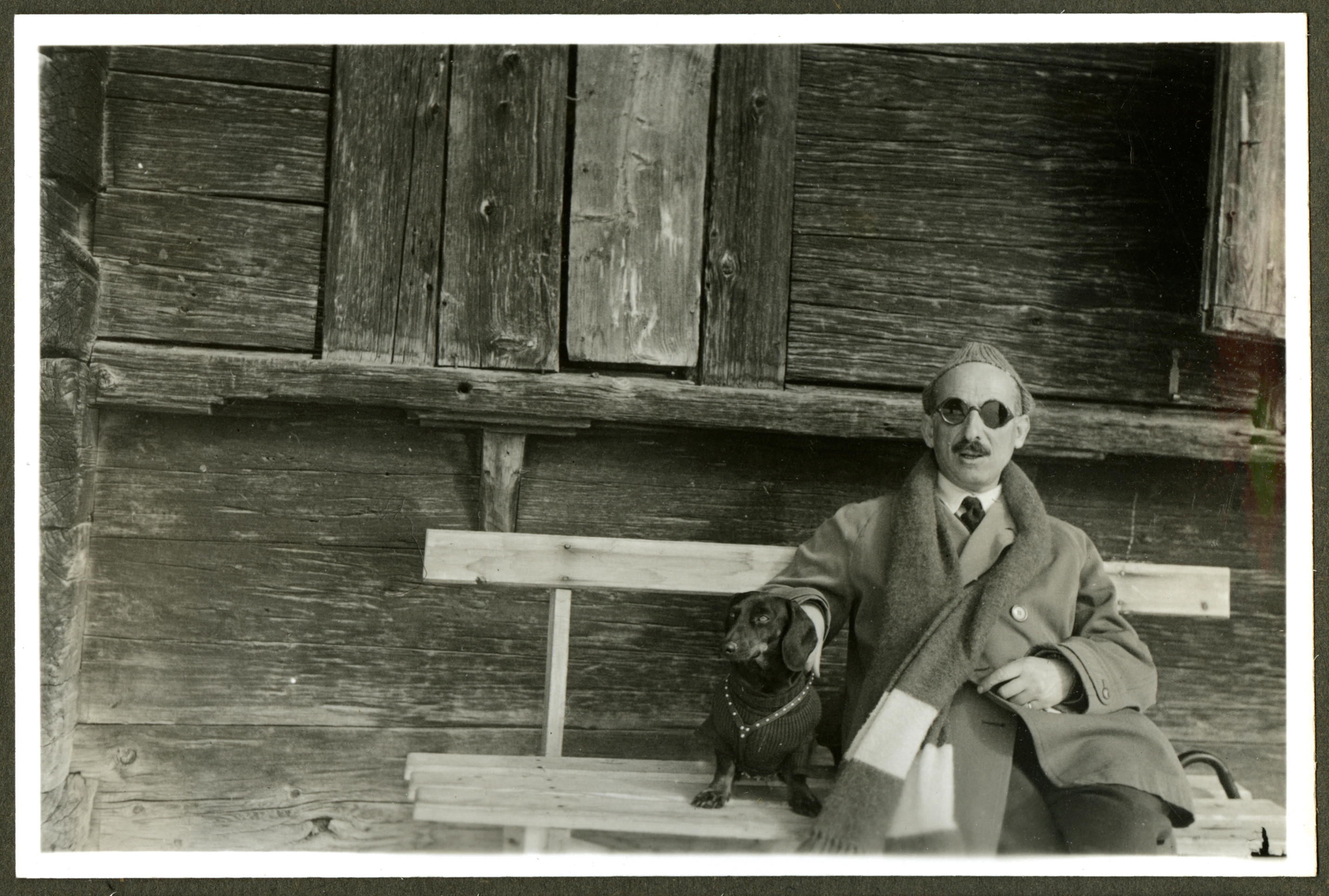 black and white photograph of a man wearing sunglasses and a coat seated on a bench with his pet Dachshund.