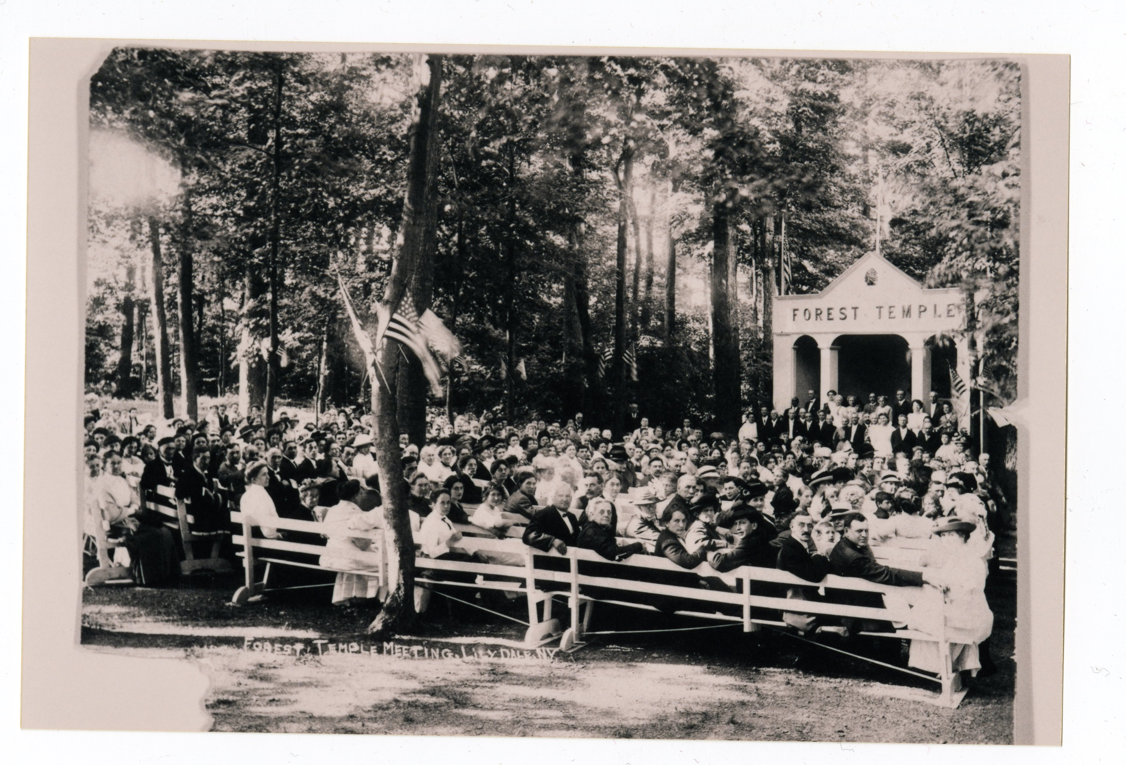 black and white photograph of crowd seated on benches in front of open-air temple structure in the woods