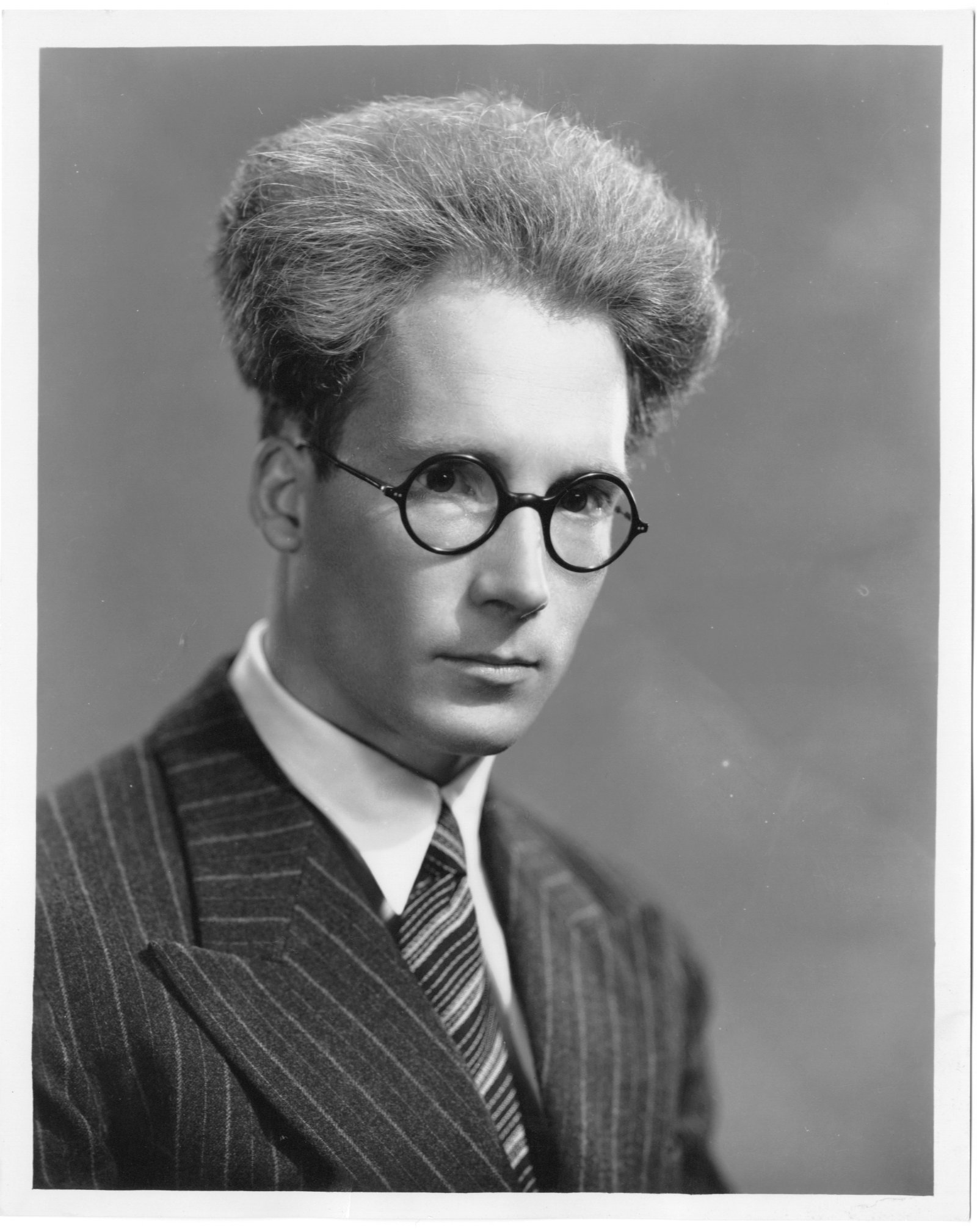 black and white portrait photograph of a man (Sigurd Rascher) with bushy hair wearing glasses and a suit and tie.