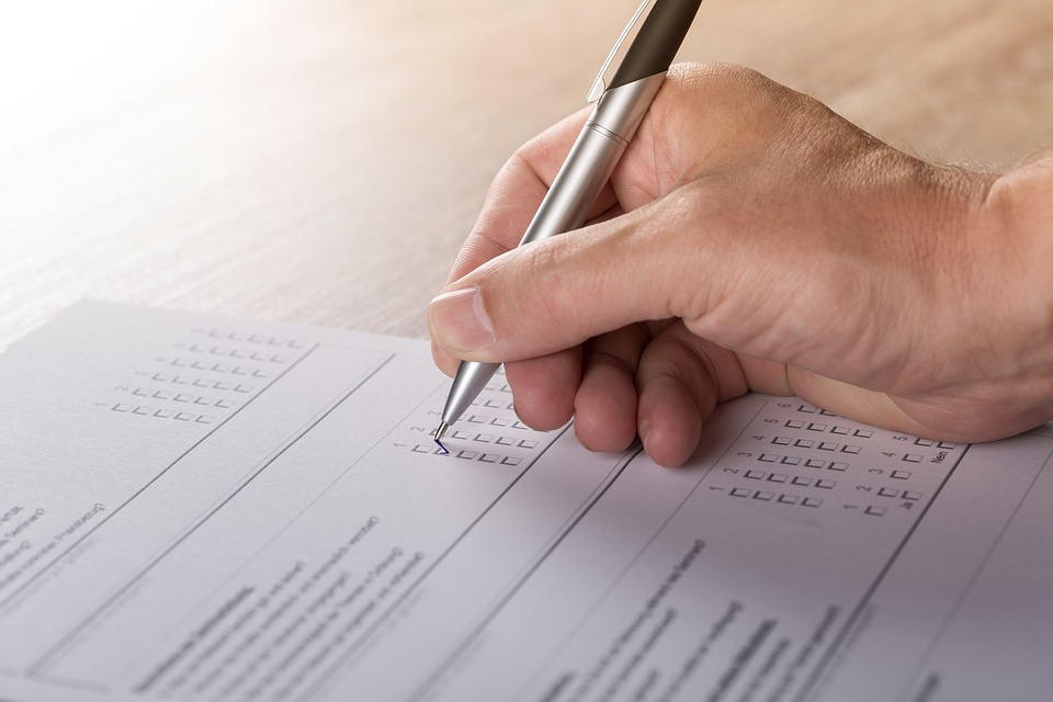 Close up of a man's hand as he fills out a paper survey with a pen.