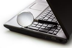 Photo of an open laptop computer with a magnifying glass.