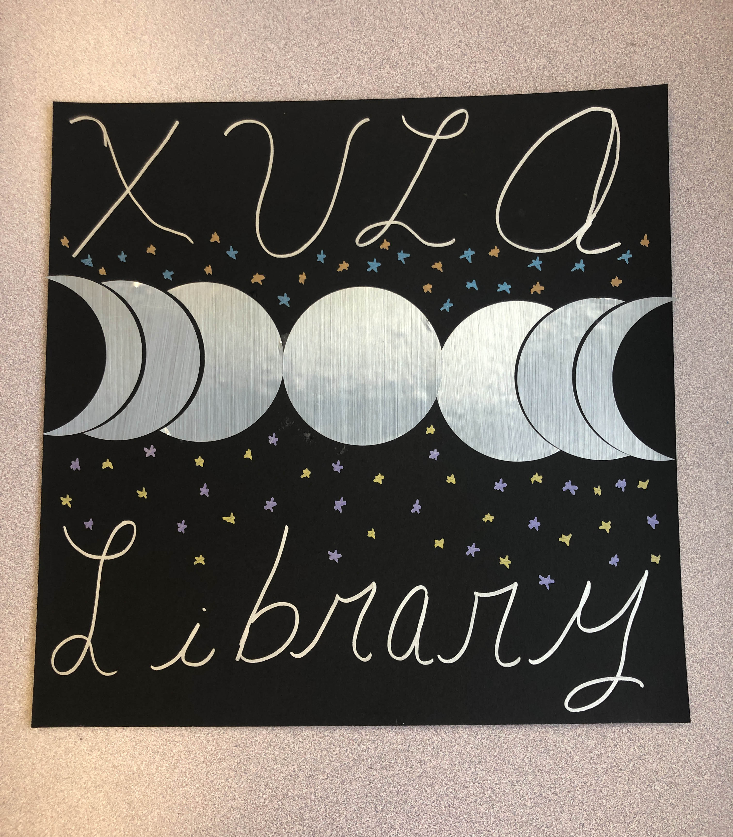 "Cardstock Poster with ""XULA Library"" with stars and the phases of the moon"