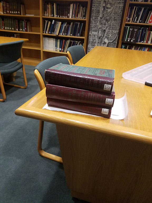 Three heavy books stacked on top of sheets of freezer paper and pictures