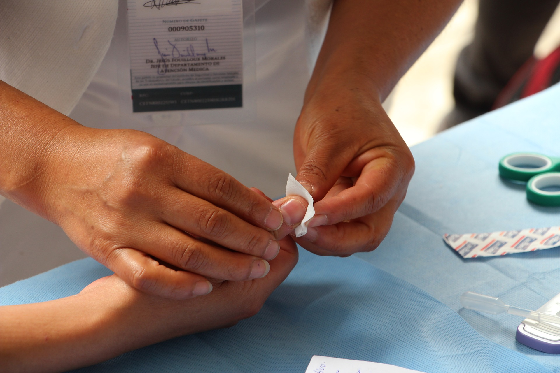 A medical professional's hands hold a small gauze square to a person's thumb.