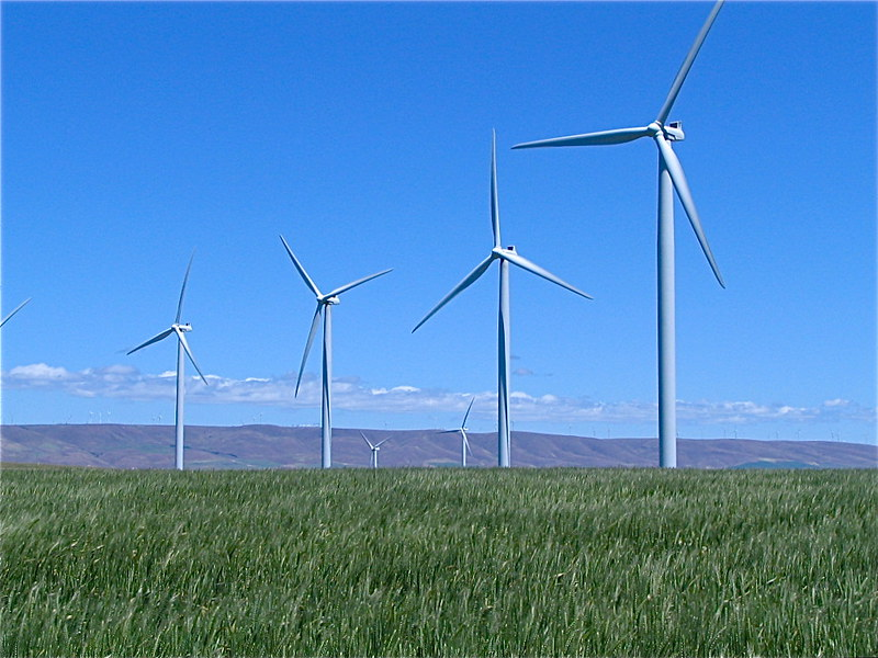 Four wind turbines against blue sky.