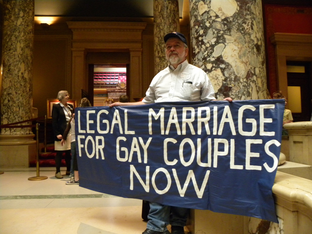 White man with legal marriage for gay couples sign