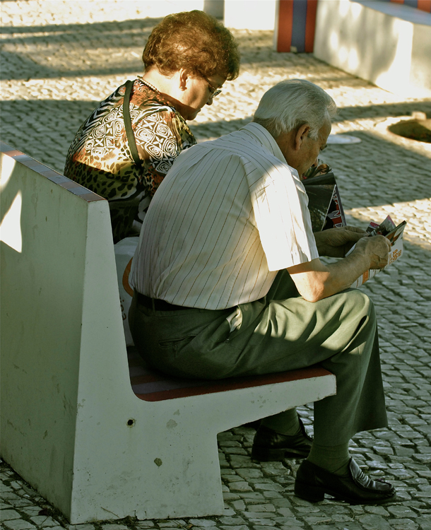 Elderly white man & woman on park bench reading