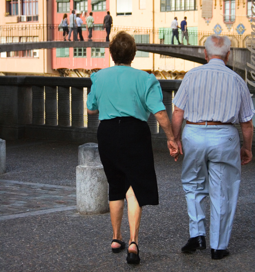 Older white male & female couple holding hands