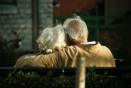 Elderly couple cuddled together on a bench