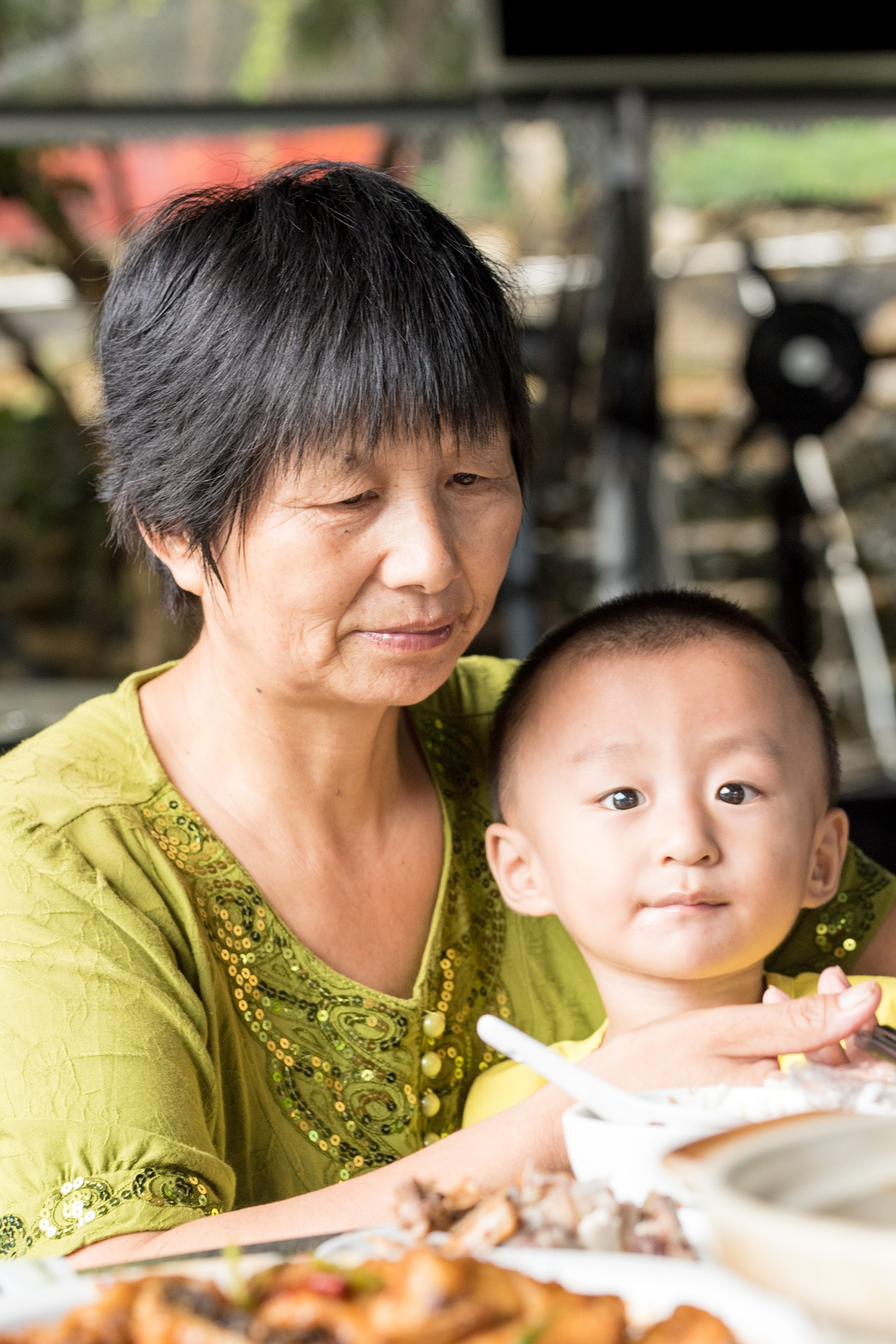 Asian grandmother with child on her lap