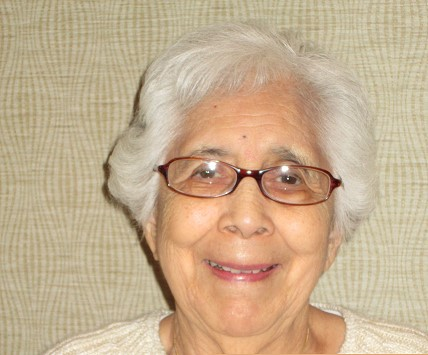 Older hispanic woman with white hair & glasses.