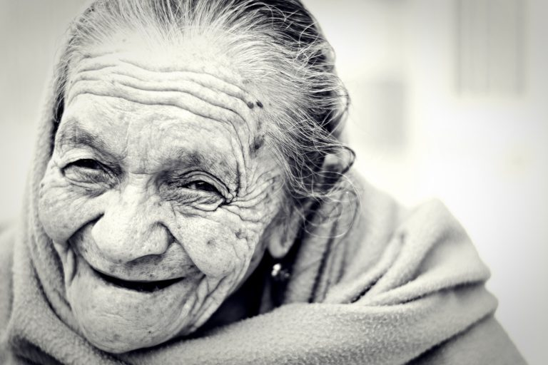 Black and white photo of smiling elderly woman, wrinkles, drooping skin, forehead lines.