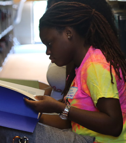 Student with a book between library shelves