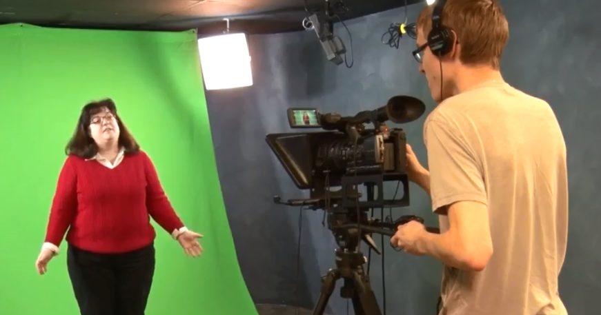 Professor in front of a green screen, cameraman