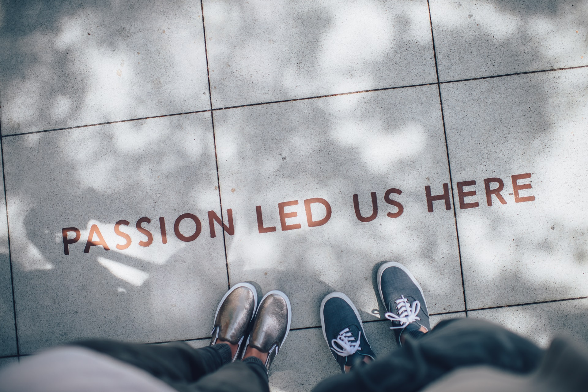 """overhead shot of two people's feet standing by words on a sidewalk, """"Passion led us here"""""""
