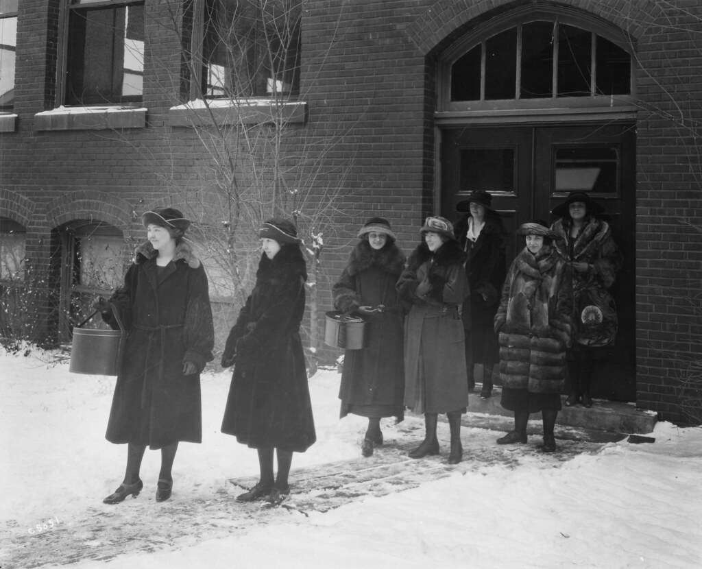 Students in 1915 wearing coats and hats in the snow outside of a college building