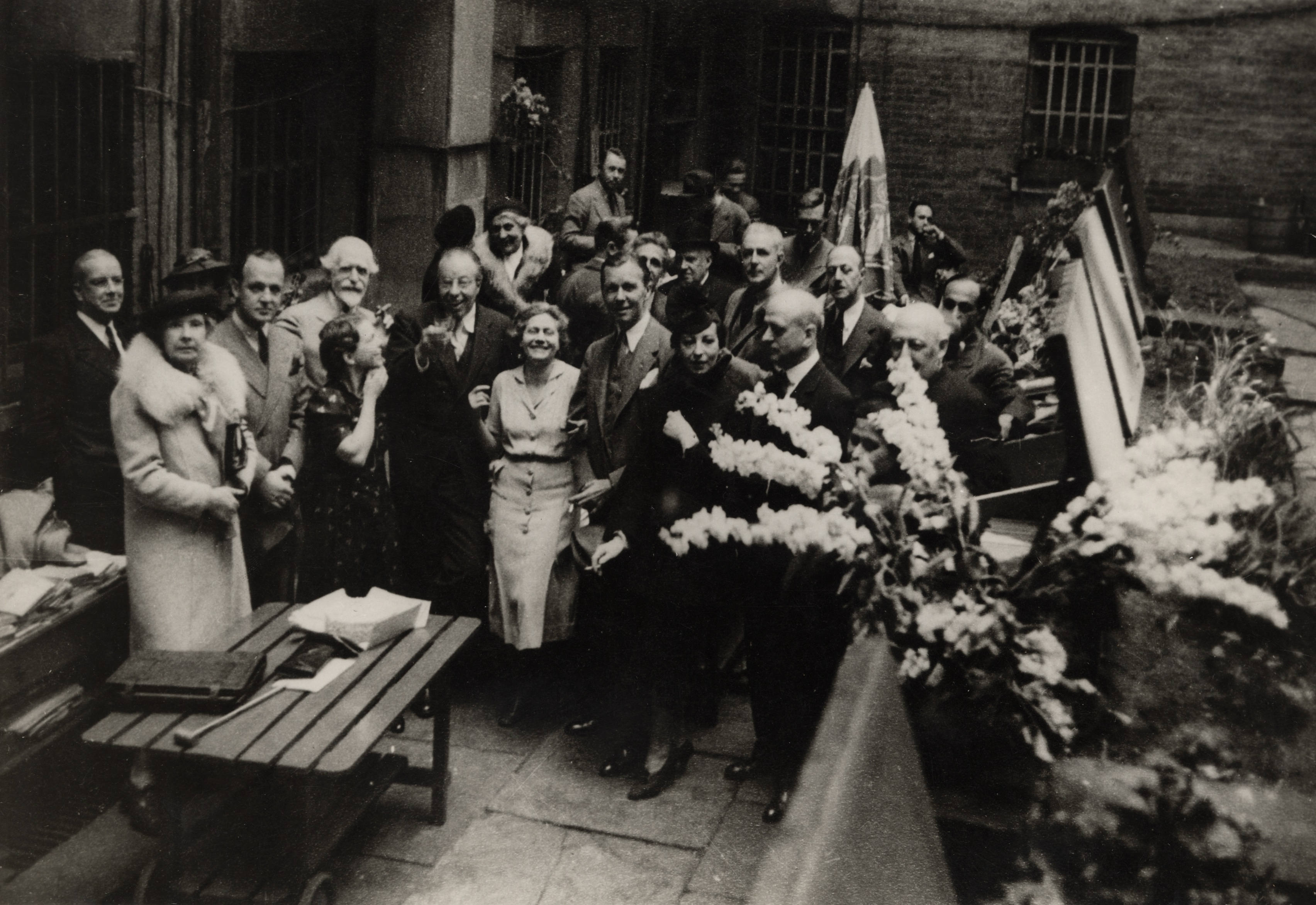B&W photograph. L to R: Buckminster Fuller, Carol Bourne, unidentified man, Wilbur Macy Stone, Kay Steele, Christopher Morley, Frances Steloff, Glenn Hunter, unidentified woman, and Mitchell Kennerley at a party in the back garden of the Gotham Book Mart. New York, n.d.