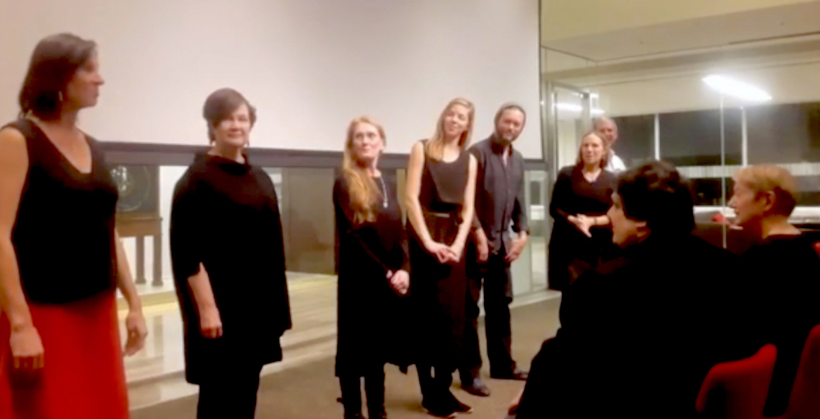 Color photograph of Orchestral Maneuvers Ensemble performing at the Kislak Center, University of Pennsylvania Libraries. A row of performers in front of a white screen.