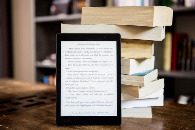 Image of a stack of books with an ebook reader
