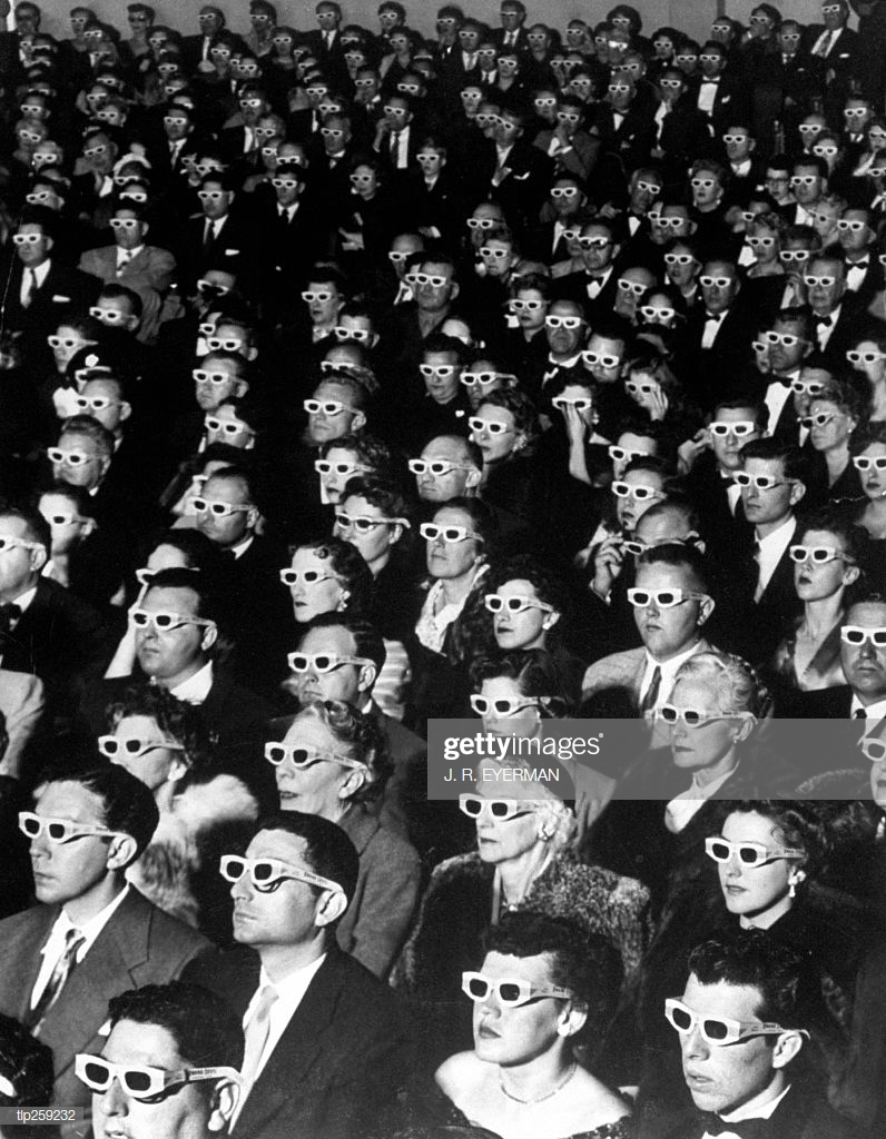 Iconic photograph of formally attired movie audience wearing 3D glasses