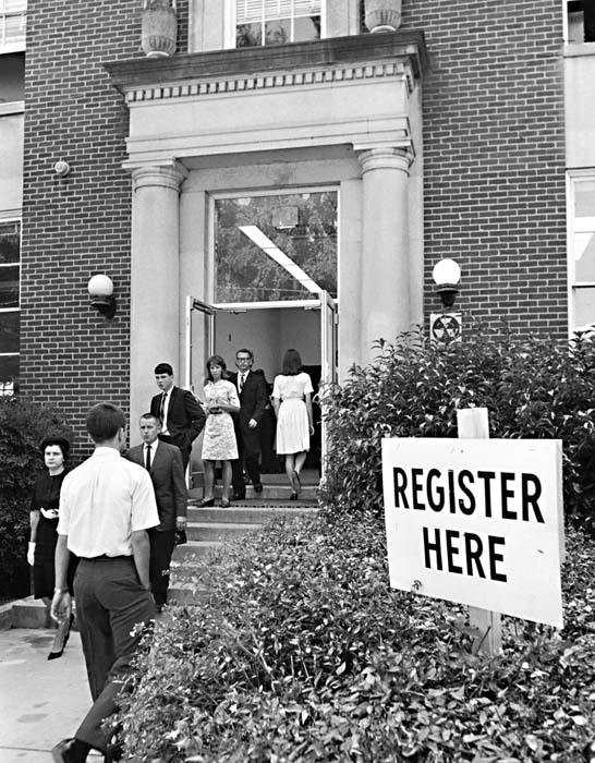 Black and white photograph of students walking into and out of building. Sign in front of building reads Register Here.