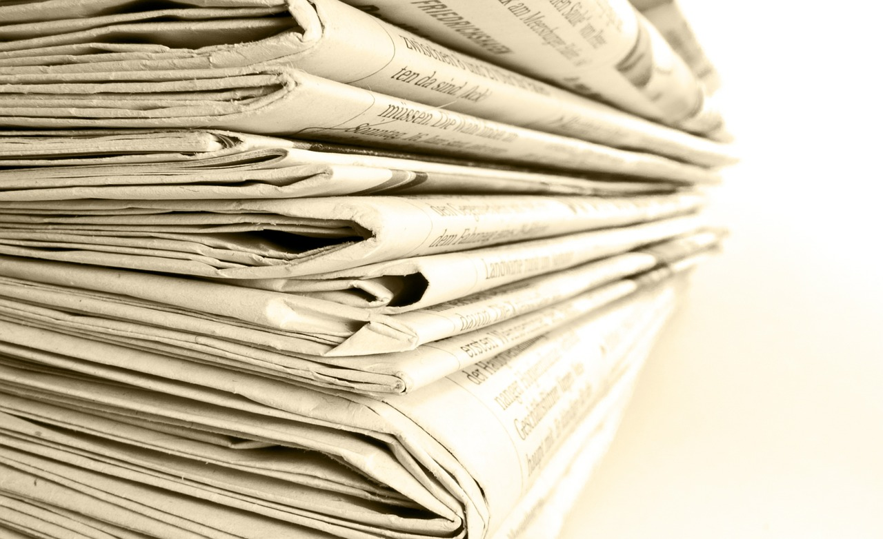 Photograph of a stack of newspapers.