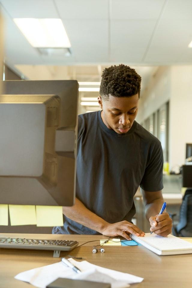 Man writing on paper near computer